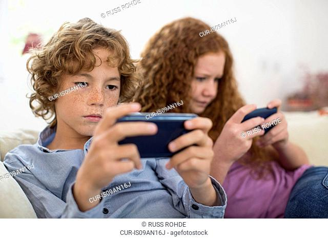 Siblings playing with handheld computer game on couch