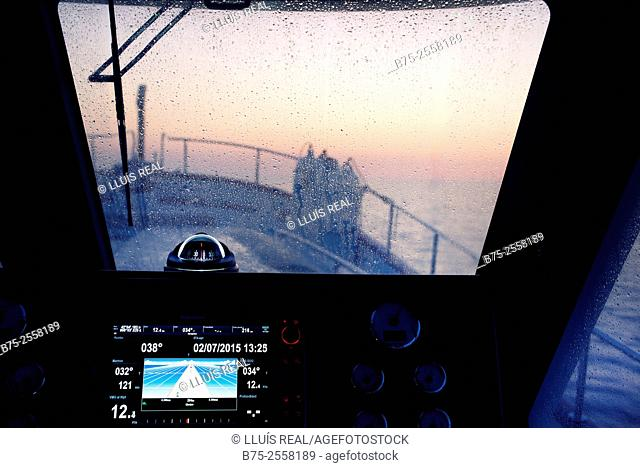 Wheelhouse of a fishing boat at dawn with autopilot and compass. Mediterranean Sea. Europe