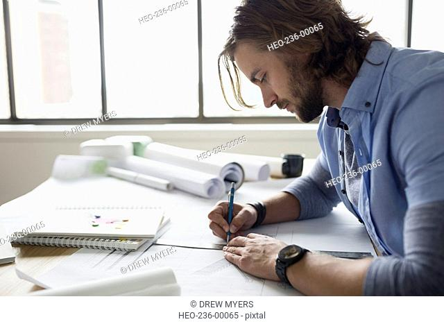 Architect drafting blueprints at table
