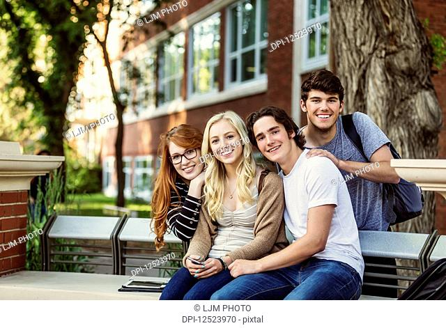 Portrait of a group of four friends sitting on a bench on a university campus; Edmonton, Alberta, Canada