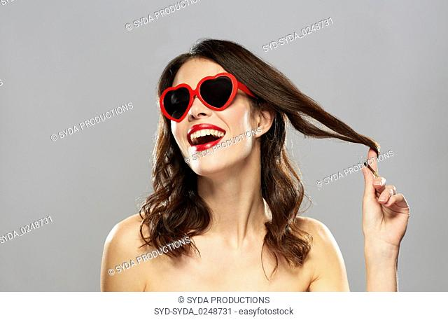 woman with red lipstick and heart shaped shades
