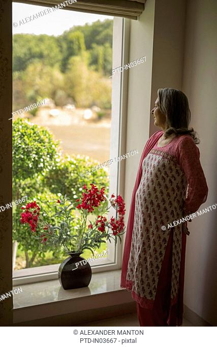 Mature woman, hands behind back looking out window