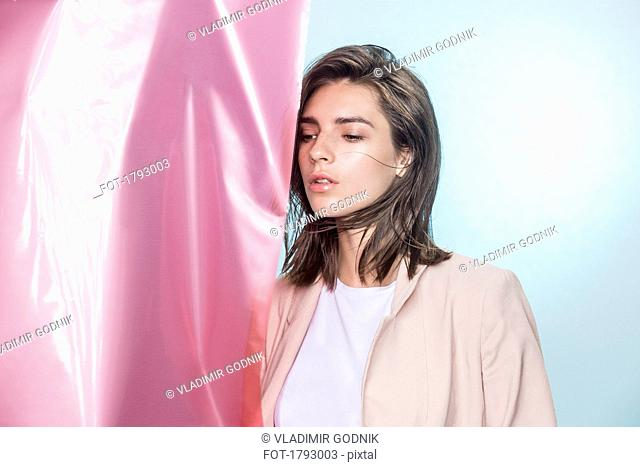 Portrait of a female fashion model posing with pink fabric and looking away