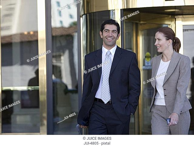 Businessman and woman leaving building, smiling