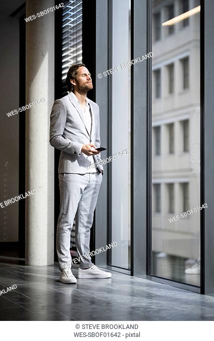 Confident entrepreneur with closed eyes standing in front of window in modern office space holding smartphone