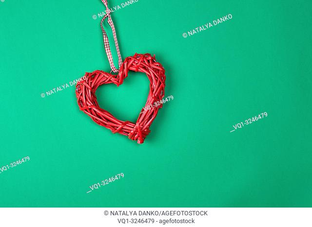 red decorative heart braided from a rod on a green background, copy space