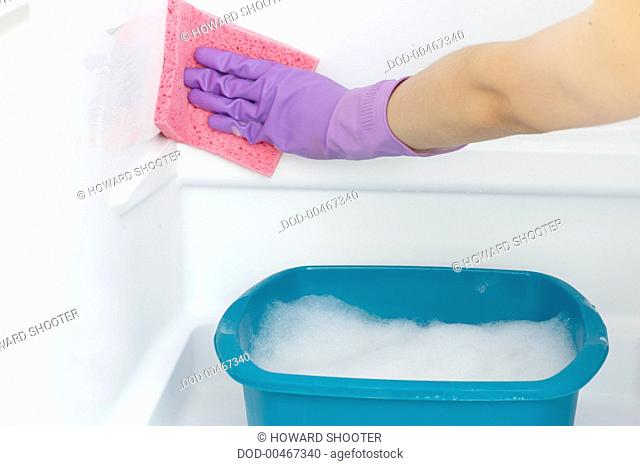 Wearing purple rubber gloves to sponge-clean inside white refrigerator with water from washing up bowl, close-up