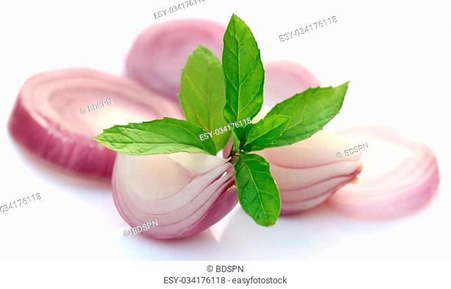 Sliced onion with mint leaves over white background