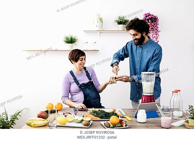 Smiling ccouple preparing healthy smoothies with fresh fruits and vegetables