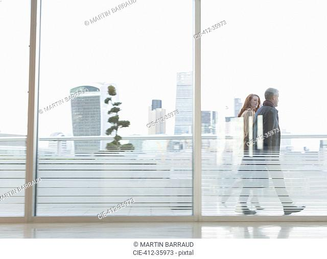 Businessman and businesswoman walking on urban highrise balcony with city view