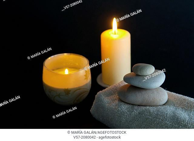 Two lit up candles, towel and stone balance. Still life