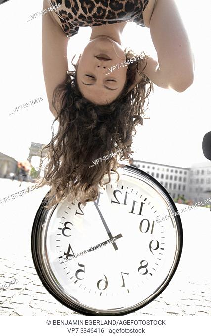 young emotional woman with closed eyes upside down with clock at street next to touristic sight Brandenburger Tor, Brandenburg gate, in Berlin, Germany