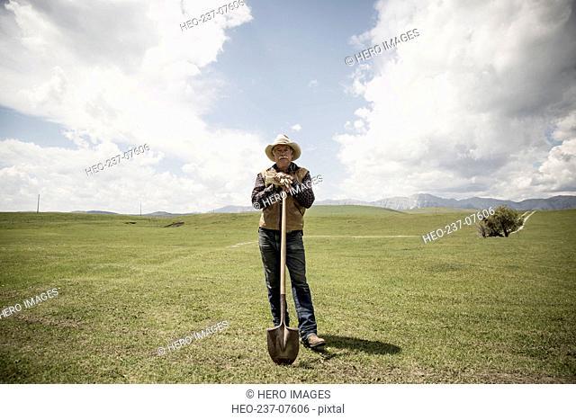 Portrait confident rancher with shove in rural field