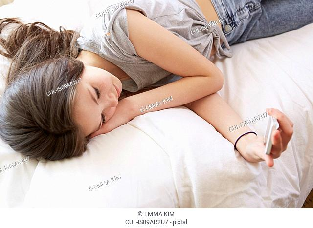 Overhead view of girl lying on bed reading smartphone text message