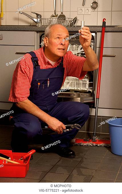 Ein Handwerker repariert den Geschirrspueler in der Kueche, 2006, Hamburg - Germany, 12/02/2006