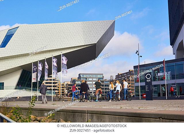 Cyclists outside the EYE Film Institute, Overhoeks, Amsterdam-Noord, Amsterdam, Netherlands. Designed by Delugan Meissl Architects it is a film museum and Dutch...