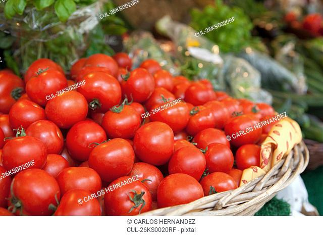 A basket full of tomatoes on a market