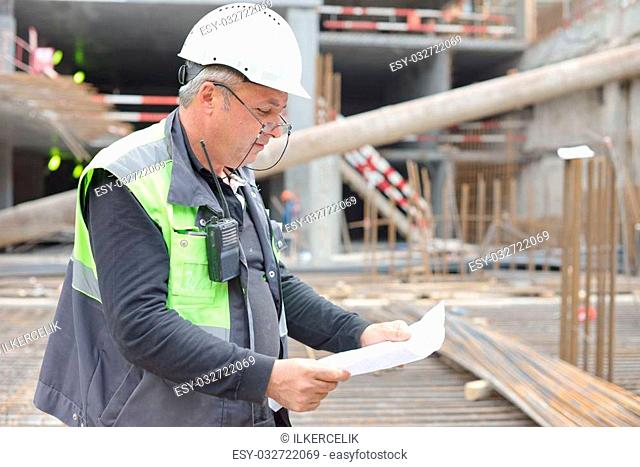 Senior Foreman at construction site is inspecting ongoing production according to design drawing