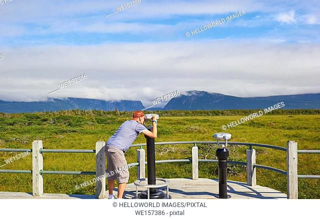 Middle aged male tourist looking through telescope at Western Brook Pond, a lake amongst the Long Range Mountains in the Gros Morne National Park a UNESCO world...