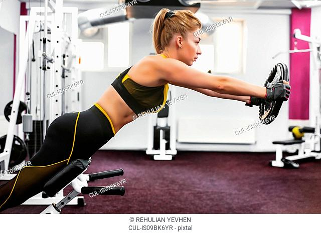 Woman lifting weight disc and leaning forward in gym