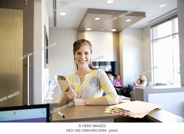 Portrait of confident receptionist holding medical records