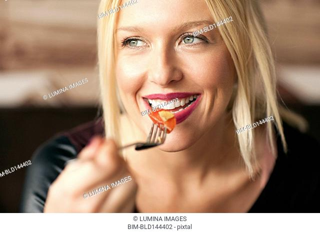 Woman eating food in cafe