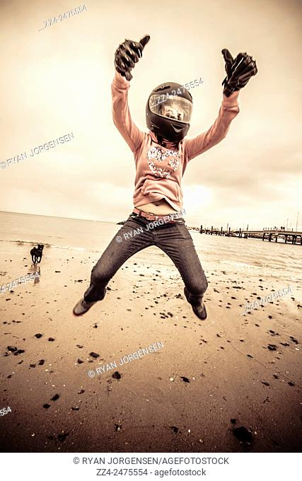 Young Woman Wearing Motorcycle Helmet and Gloves Leaping Into Air on Overcast Beach with Dog and Pier in Background