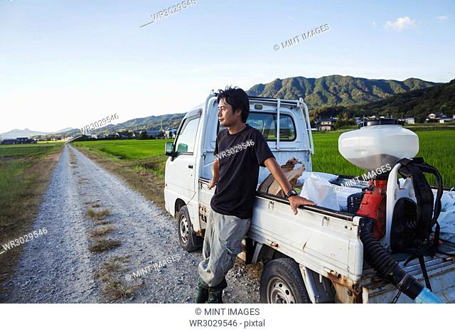 A rice farmer standing by his truck looking across the flat landscape, rice paddies and a village in the distance