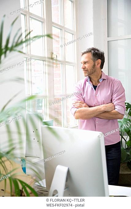 Man looking out of window in office