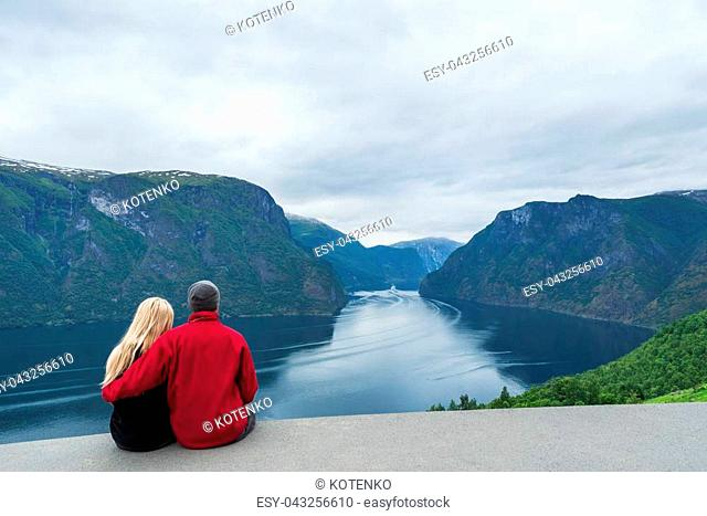 Panorama of Aurlandsfjord. Tourist couple enjoys a beautiful view of the fjord and mountains