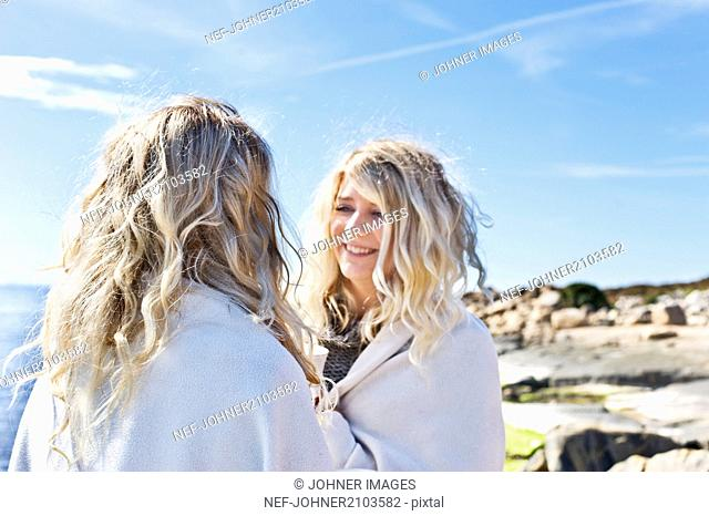 Twins looking at each other on beach