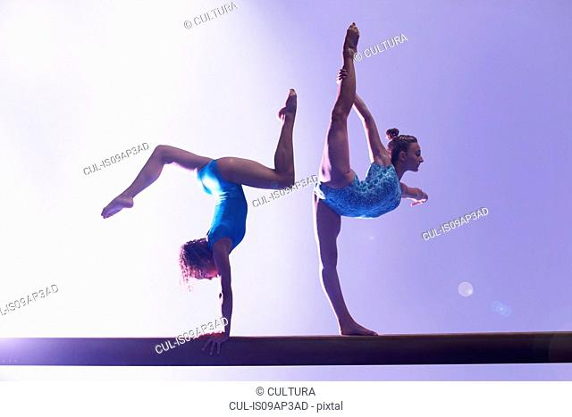Gymnasts doing routine on bar