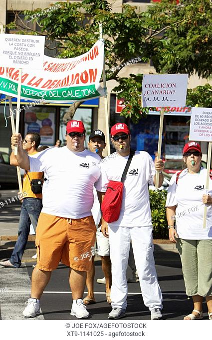 vertical three Spanish protesters demonstrate holding placards with red hats blowing whistles in Santa Cruz Tenerife Canary Islands Spain