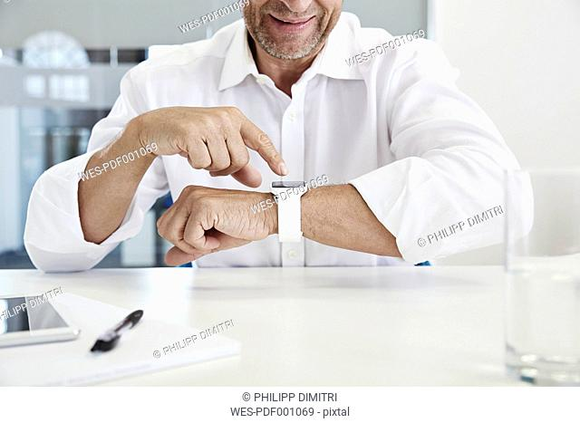 Businessman in office looking at smartwatch