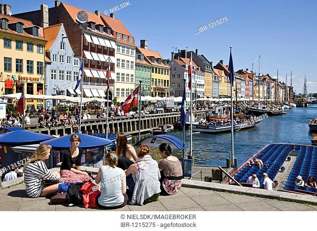 Tourists relaxing in Nyhavn, Copenhagen, Denmark