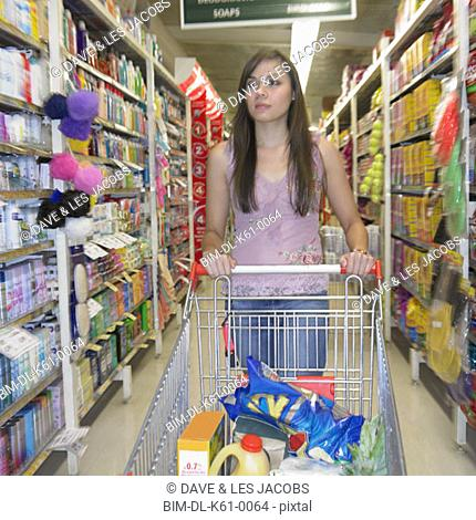 Woman with shopping cart at supermarket, Perth, Australia