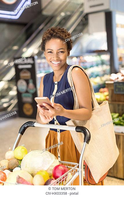 Portrait smiling young woman using cell phone, grocery shopping in market