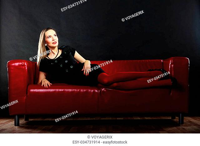 Elegant fashion outfit. Fashionable woman long legs in red vivid color pantyhose relaxing on couch indoor on black