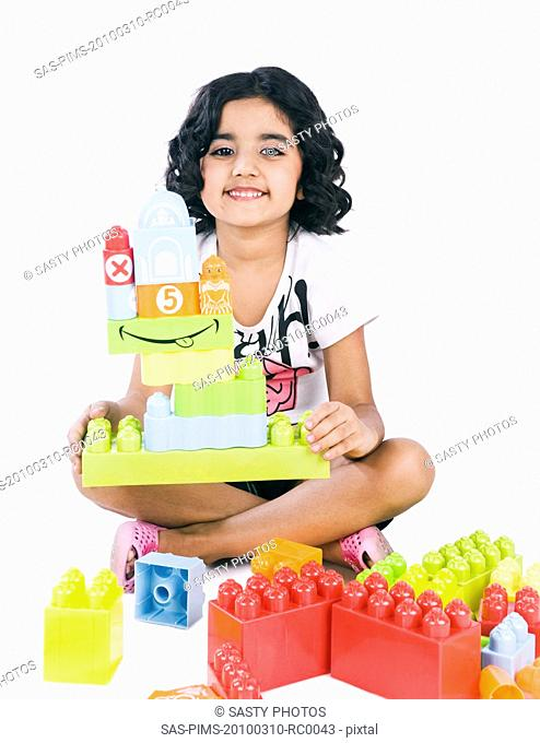 Portrait of a girl playing with building blocks