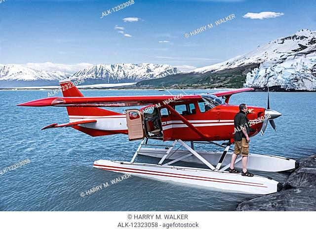 Man standing on the float of a Cessna 206, Lake George, Colony Glacier, Southcentral Alaska, USA