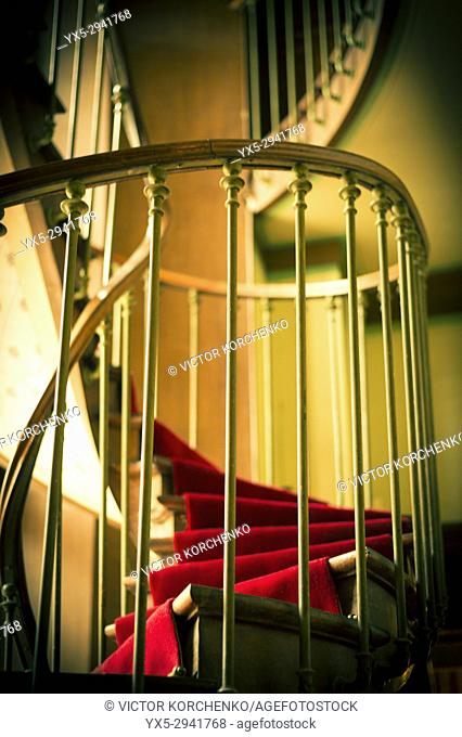 Spiral staircase with a red carpet