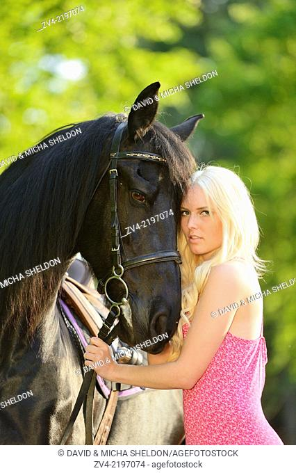 Young woman standing beside a Friesian horse in late sunlight