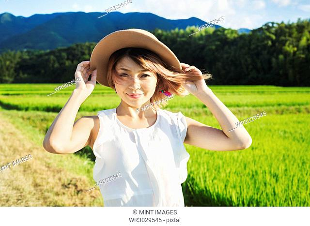A young woman holding a straw hat on her head, hair blowing in the wind, in open space by rice paddy fields