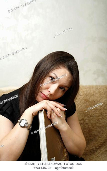 pretty brunette girl indoors on modern sofa