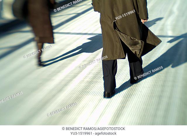 Man and woman walking separtely across the Millennium Bridge, London, England, Europe