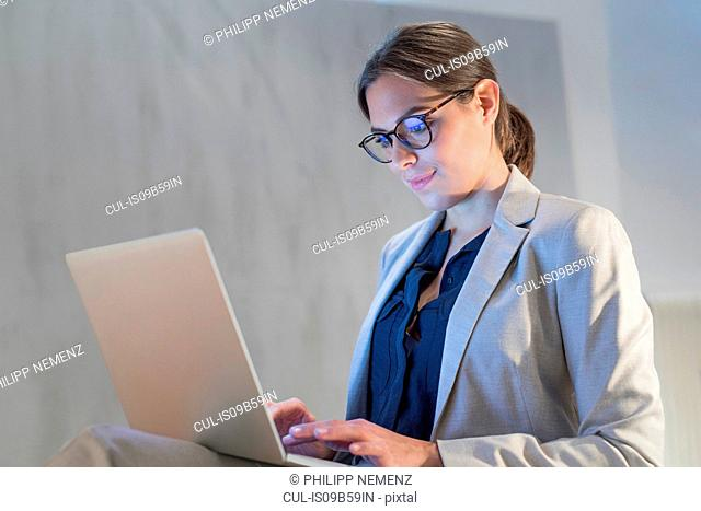 Young businesswoman at desk typing on laptop