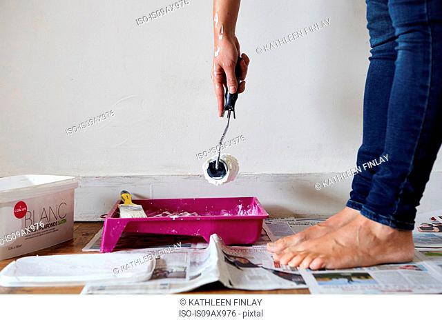 Woman painting, dipping paint roller in paint, low section