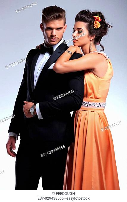 young fashion couple with woman resting on his shoulder while he looks into the camera. on gray background