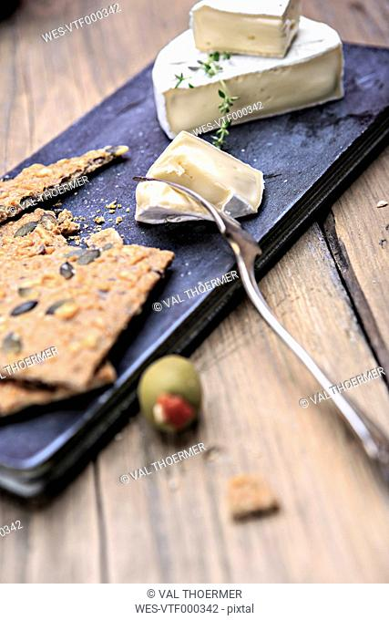 cheese plate and olives on chopping board