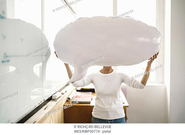 Woman standing in office, holding inflatable speech bubble in front of her face
